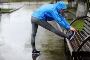 Women stretching her hamstring in the rain